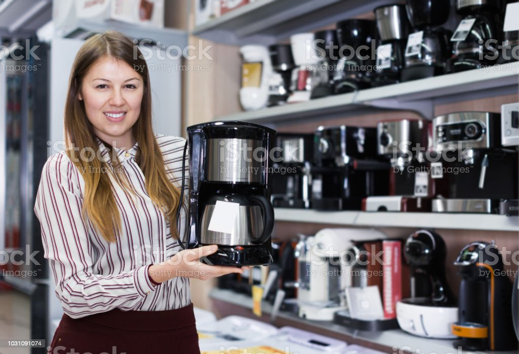 Positive salesgirl suggesting coffee brewer in store of kitchen...