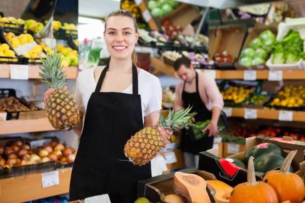 Positive Verkäuferin in Schürze bietet frische Ananas im Obstladen – Foto