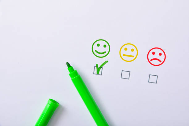 Positive satisfaction with green marker represented with emoticons on paper Positive satisfaction marked with green marker pen represented with colored emoticons on white paper. Horizontal composition. Top view. positive emotion stock pictures, royalty-free photos & images