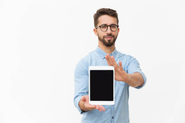 Positive satisfied tablet user showing blank screen stock photo