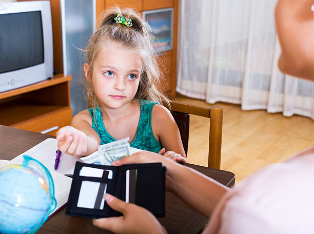Positive schoolgirl asking money Portrait of little schoolgirl asking money for a day allowance stock pictures, royalty-free photos & images