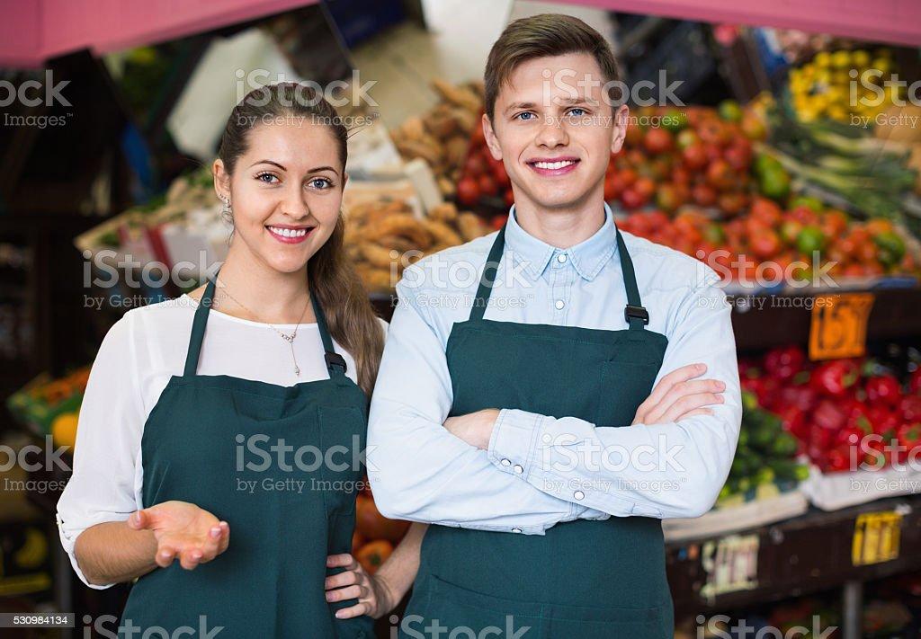 Vendedores positiva com legumes e frutas na exibe - foto de acervo