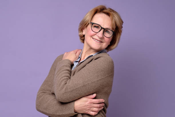 Positive senior caucasian woman in glasses smiling, keeping arms around herself. stock photo