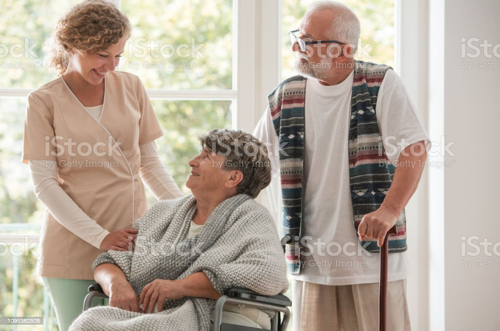 Positive senior couple with their caregiver in nursing home for...