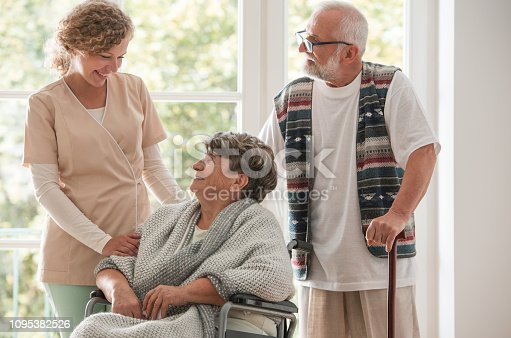 istock Positive senior couple with their caregiver in nursing home for elderly 1095382526