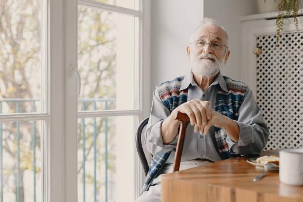 Positiver Senior Großvater mit grauen Haaren und Bart sitzen zu Hause – Foto