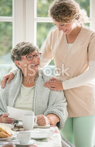 istock Positive senior lady siting at table and smiling to her young nurse 1080278256