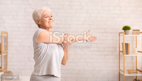 Morning work-out. Positive senior lady warming up her hands at home, empty space