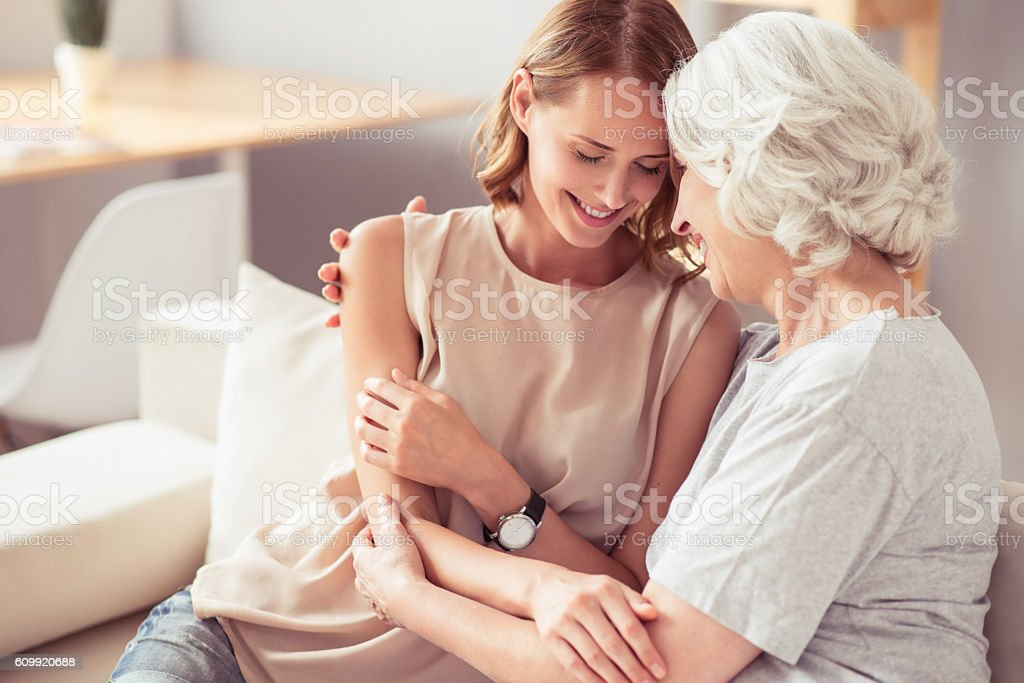 Positive senior mother and her daughter embracing stock photo