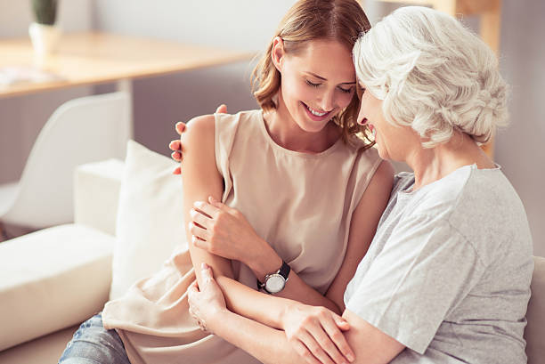 positive senior mother and her daughter embracing - daughter stock photos and pictures