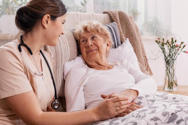 Positive senior woman lying in bed helpful doctor in beige uniform picture id1146312533?b=1&k=6&m=1146312533&s=612x612&w=0&h=ed62qe3oqyn9yrkikflhildgtva3lpofinvviyqk0h8=