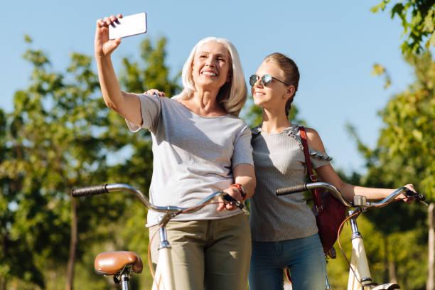 positiven senior frau machen fotos mit ihrer hübschen enkelin - happy weekend bilder stock-fotos und bilder