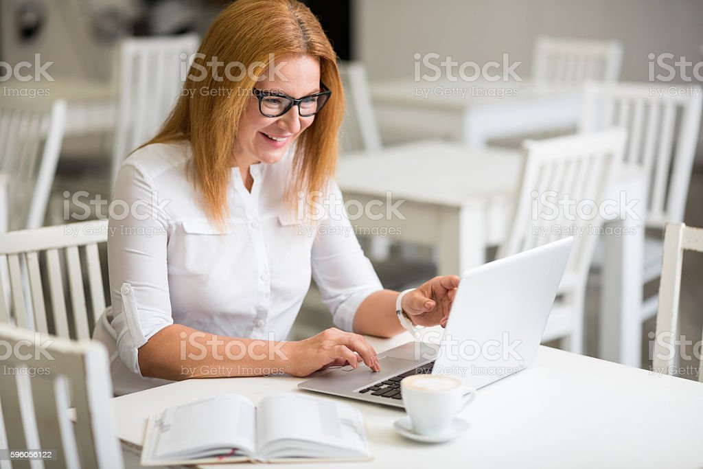 Positive senior woman sitting at the table royalty-free stock photo
