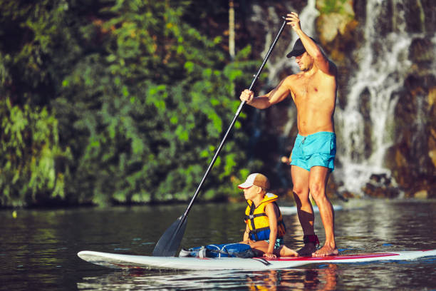 positive smiling boy in rashguard and his young father enjoying stand up paddleboarding stock photo