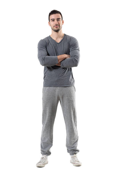 positive smiling young fit sporty man with crossed arms looking at camera. - sweatpants stock-fotos und bilder