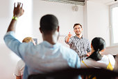 Yes you. Cheerful friendly speaker conducting a business workshop and pointing to a student raising his hand