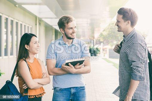 istock Positive students talking outdoors during break 981653990