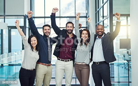 Portrait of a diverse team of colleagues cheering at work