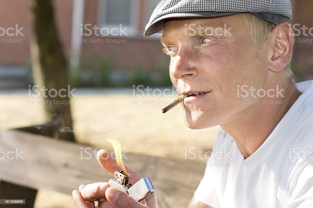 Positive thoughtful man lighting a brown cigarette royalty-free stock photo