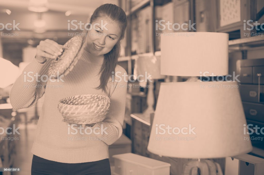 Positive woman buyer holding wicker basket royalty-free stock photo