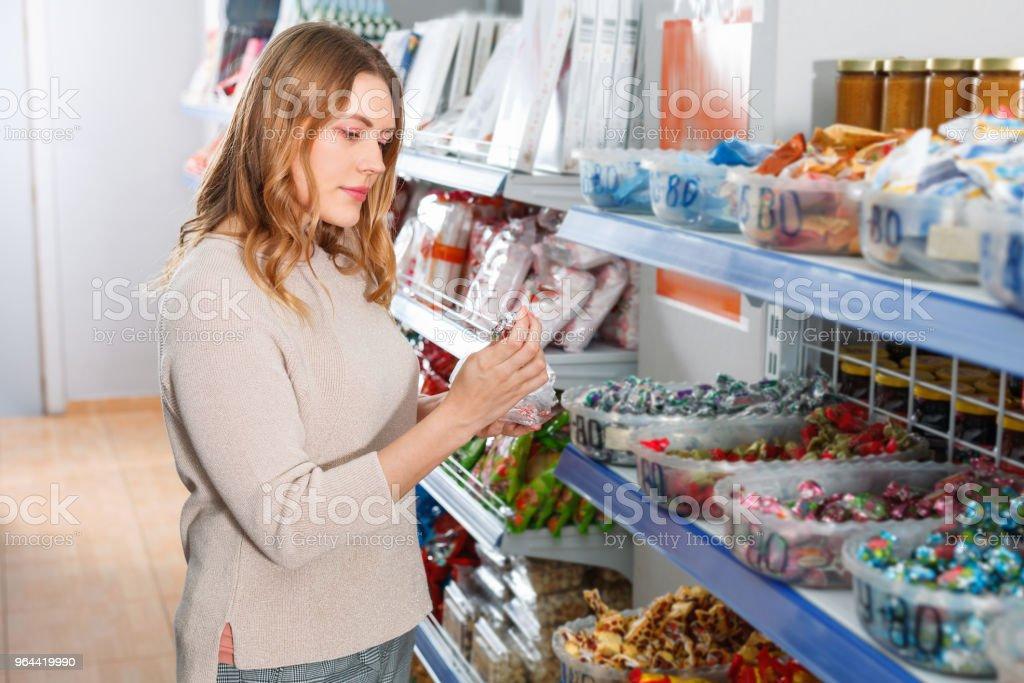 Positieve vrouw koper plukken van verschillende snoepjes in cellofaan tas in winkel - Royalty-free Binnenopname Stockfoto