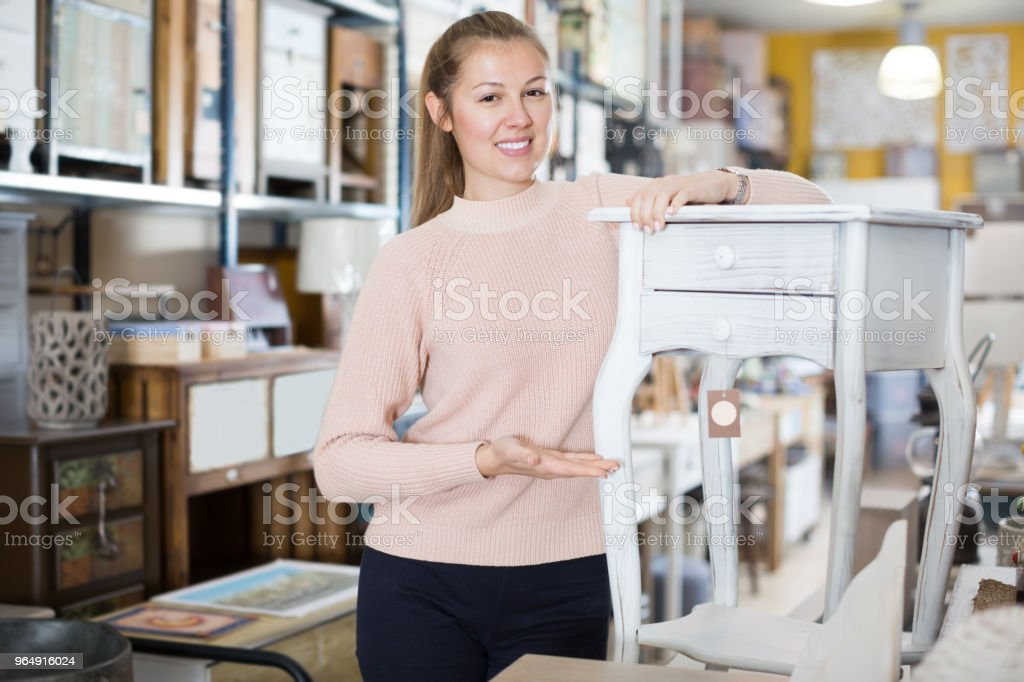Positive woman customer choosing dressing table in shop royalty-free stock photo