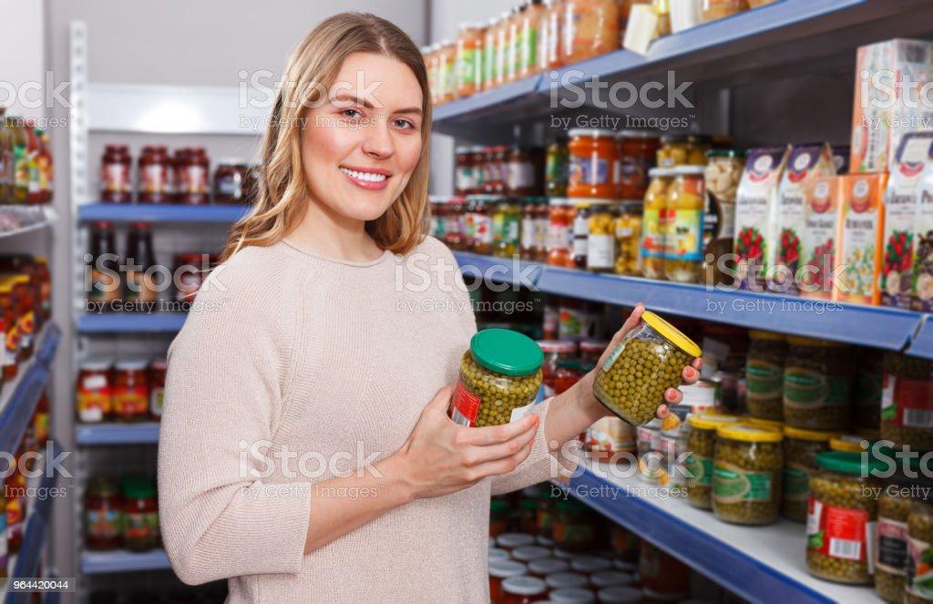 Cliente positivo mulher segurando picles mercadorias numa loja de alimentos - Foto de stock de 30 Anos royalty-free