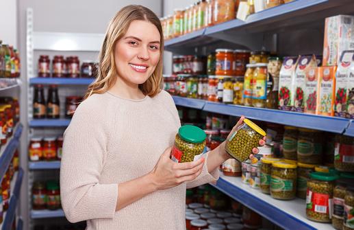 Foto de Cliente Positivo Mulher Segurando Picles Mercadorias Numa Loja De Alimentos e mais fotos de stock de 30 Anos