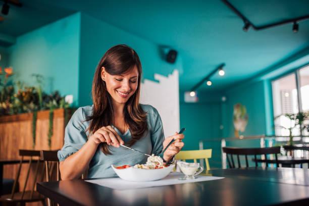 Mujer positiva comiendo ensalada en un acogedor café. - foto de stock