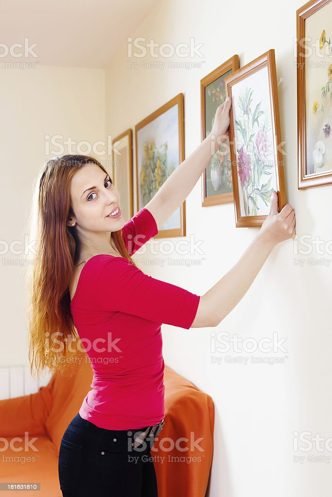 Positive  woman in red hanging the art pictures royalty-free stock photo