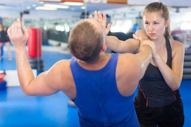 positive woman is fighting with trainer - combat sport stock pictures, royalty-free photos & images