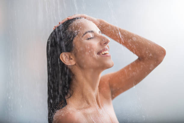 Positive woman taking hot shower stock photo
