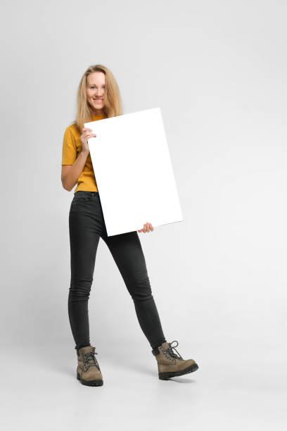 positieve vrouw met mockup poster - zwarte spijkerbroek stockfoto's en -beelden