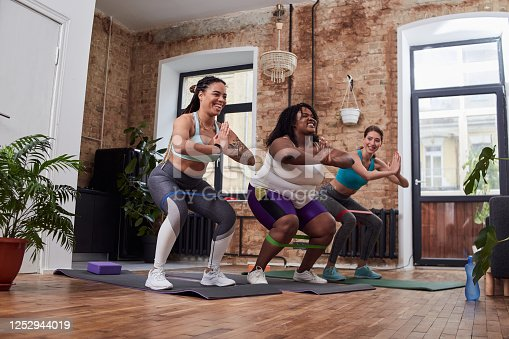 Delighted ladies keeping palms together in front of chest and using elastic bands while doing squats on exercise mat