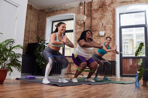 Positive women stretching with deep bends in home atmosphere stock photo