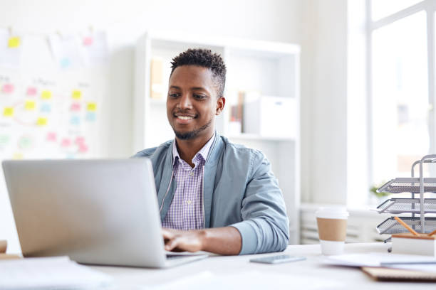 Positive young African-American male copywriter in casual jacket typing on laptop and sitting at table while working on article in office Positive African copywriter in office copywriter stock pictures, royalty-free photos & images