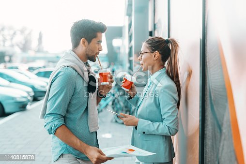 Positive young businesspeople standing outdoors, discussing and drinking coffee to go. Woman holding tablet and man holding paperwork.