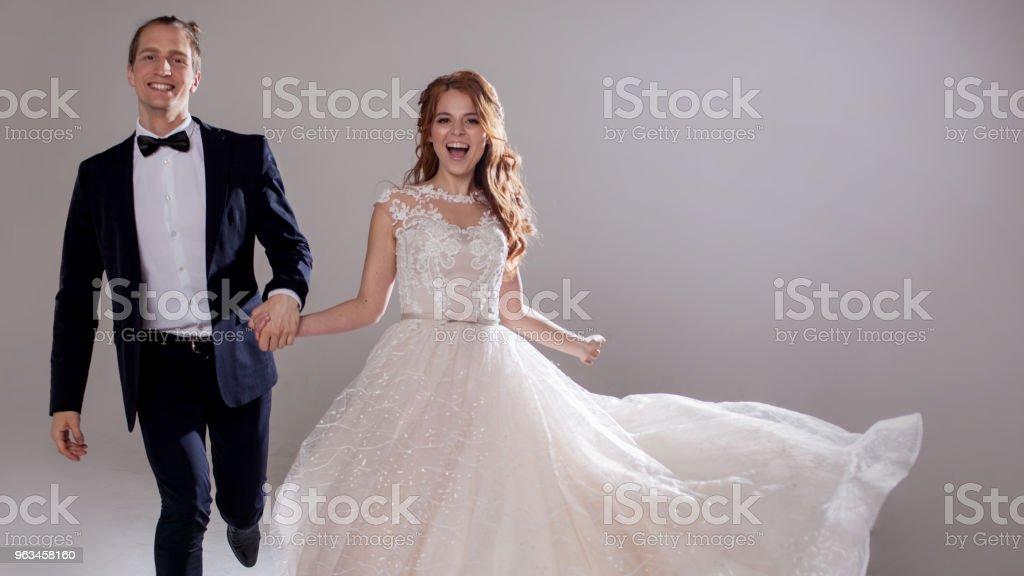 Pareja joven positiva riendo y bailando juntos. La pareja en el estudio un fondo claro. - Foto de stock de Alegría libre de derechos