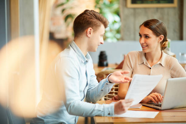 Positive young entrepreneurs in casual outfits sitting at table in coffee shop and discussing contract stock photo