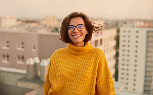 Positive young lady on roof stock photo