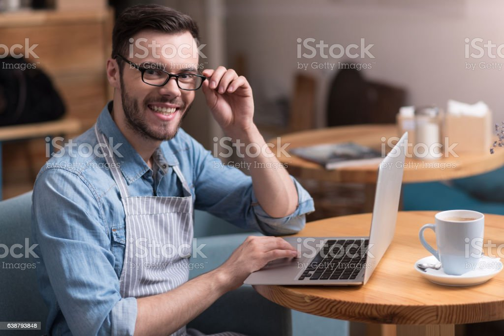 Positive young man touching glasses and using laptop. stock photo