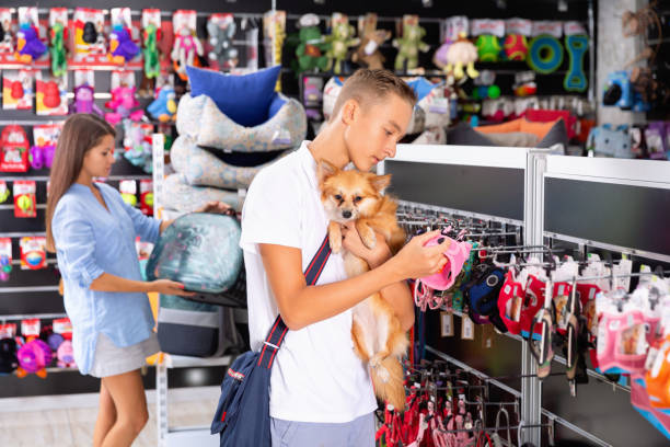 positive young man with dog in pet store during shopping with man - pet shop and dogs not cats stock pictures, royalty-free photos & images