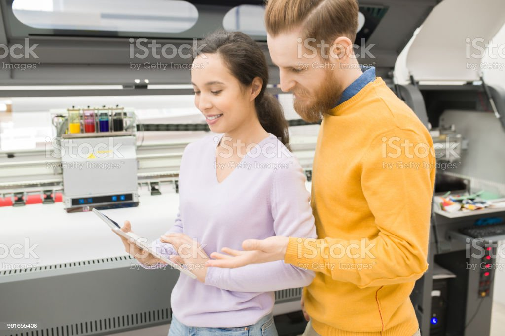 Positive young printing specialists testing new mobile app on tablet while working with large format printing stock photo