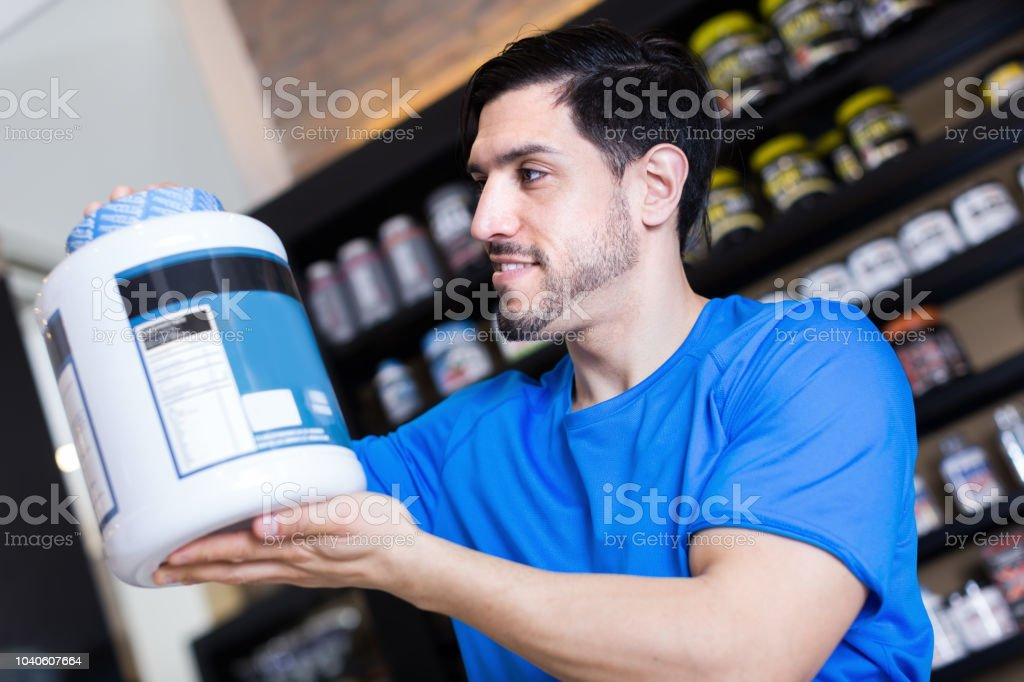 Positive young sport man buying sport supplements in shop stock photo