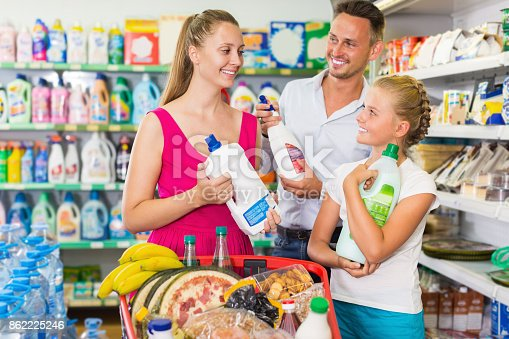 istock Positive young woman and male with girl choosing detergent 862225246