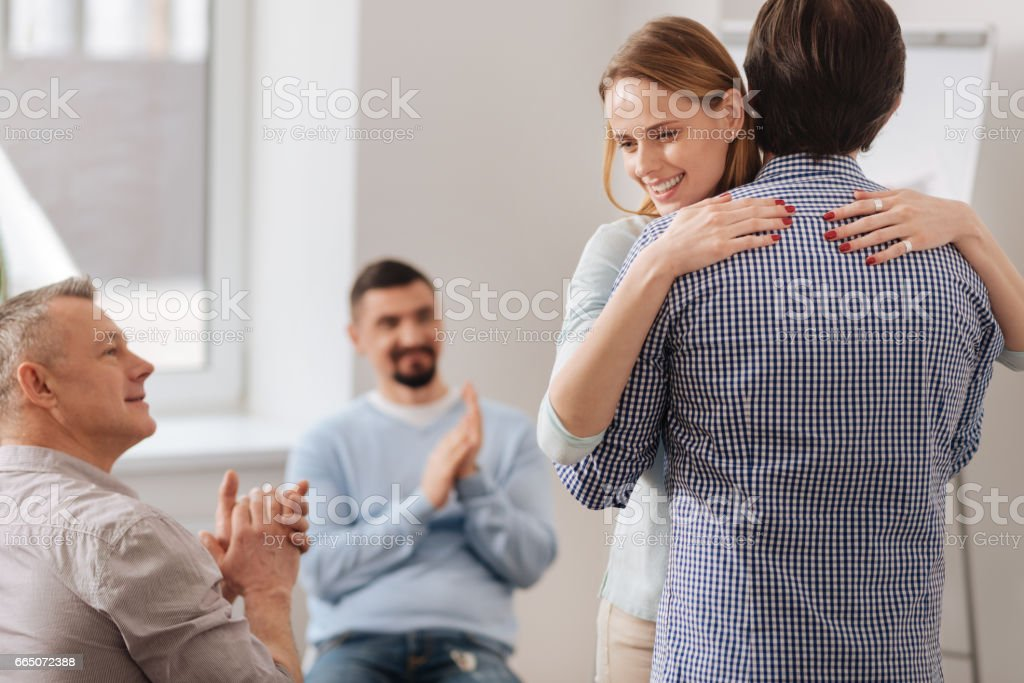 Positive young woman holding hands on male shoulders stock photo