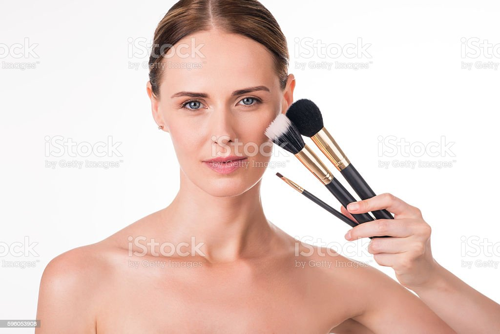 Positive young woman holding makeup brushes royalty-free stock photo