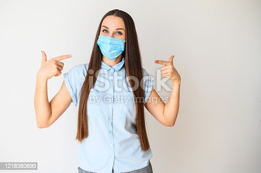 Safety during a pandemic, epidemic, seasonal flu. Positive young woman in a medical mask on her face points her fingers to the mask. The call to protect yourself