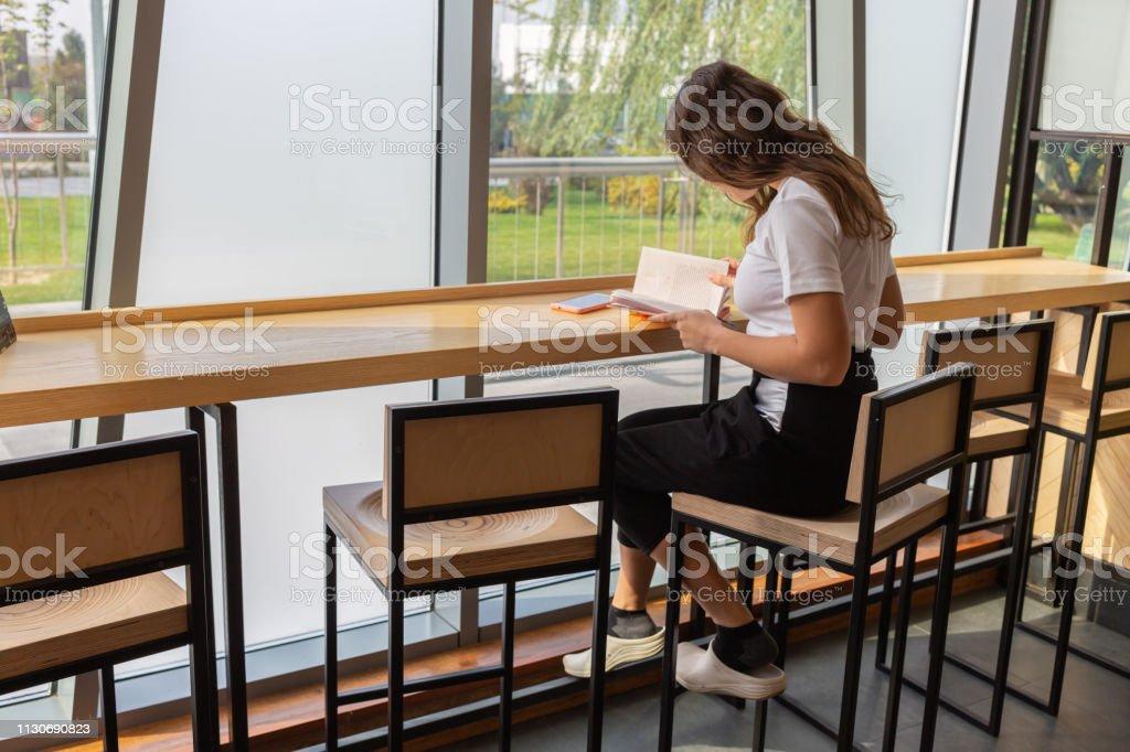 Positive junge Frau in stilvollen Brillen träumt am Tisch mit geöffnetem Buch im stilvollen Coworking Space. Lächelnde schöne Hündin in Brille schaut beim Lesebeständler weg – Foto