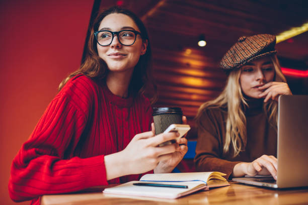 Positive young woman looking away holding coffee cup cooperating with colleague on freelance project, female students learning in cafe interior using modern technology doing homework task together stock photo